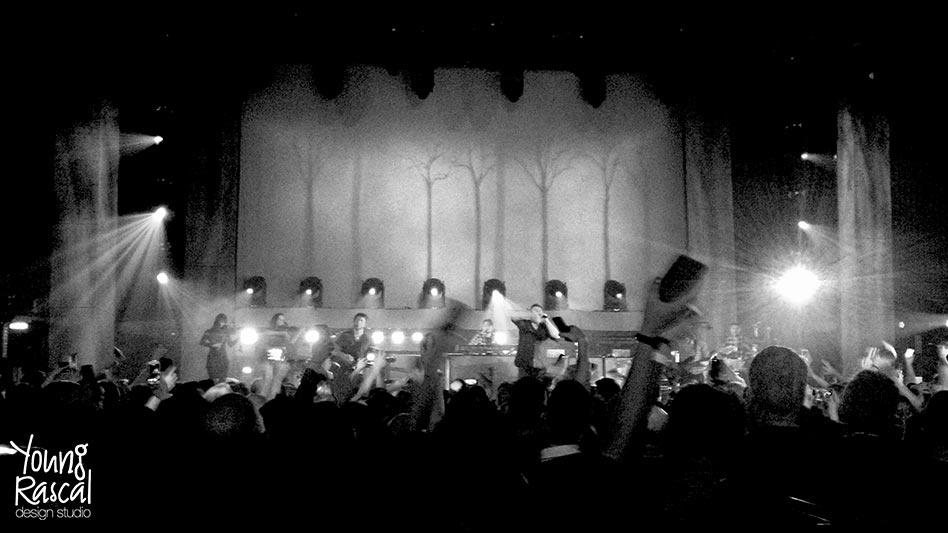 Black and white still of the band, Elbow, performing 'My Sad Captains' before a Young Rascal animated forest backdrop.