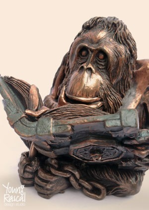 Young Rascal sculpture of Terry Pratchett's 'Librarian'. The bronzed orang-utan sits crossed legged, hand on chin, reading a heavy book from the Unseen University.