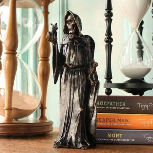 Bronzed resin Young Rascal sculpture of Terry Pratchetts, DEATH with kitten, standing before the author's books and sand filled time glasses.